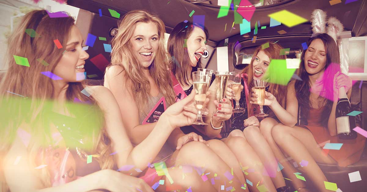 Group of women in the back of a limo celebrating a hens party.