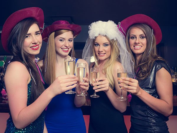 Young women on a hens party with hats on while bride to be is wears a white veil