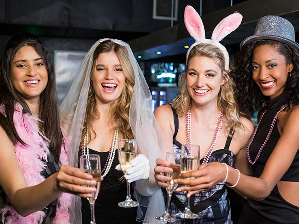 Four women with hens party accessories on including bunny ears, party hat, veil, feather boa and necklaces