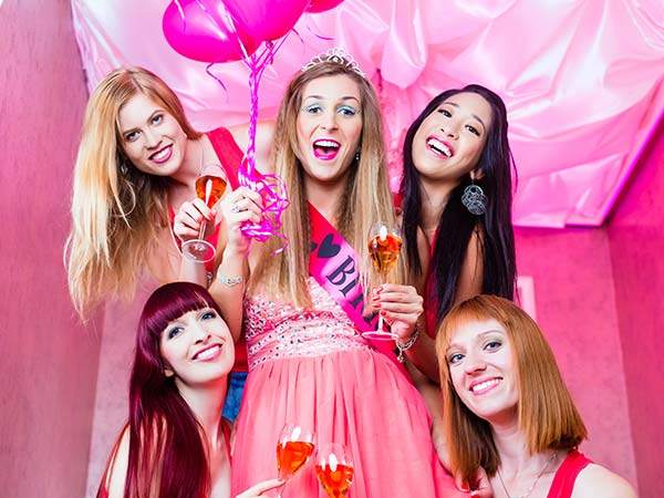 Bride to be with sash on holding balloons surrounding by her close friends all dressed in pink