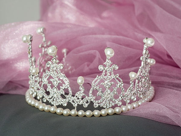 Gorgeous silver tiara with peals sitting on pink veil